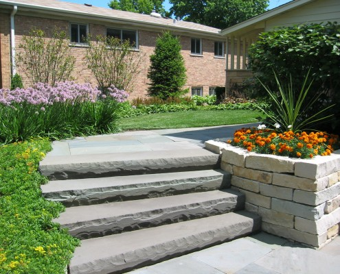stone stairway and retaining wall with flower beds